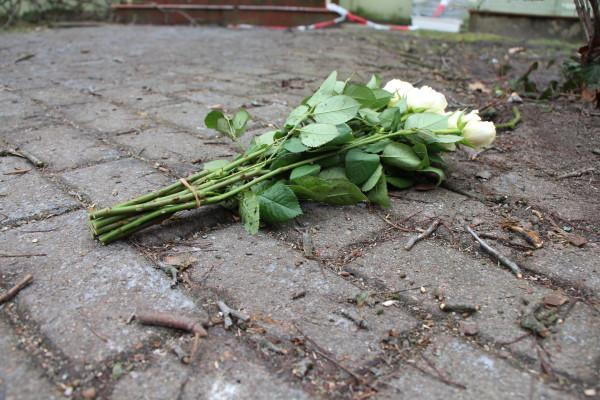 Vor dem Haus liegen Blumen von Trauernden. Foto: Till Heinsohn