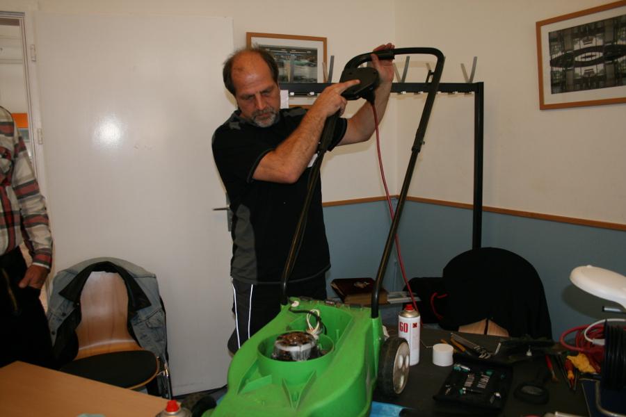 Jürgen Fink, gelernter Betriebsschlosser, inspiziert einen Rasenmäher. Foto: Anja von Bihl