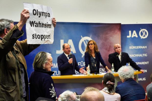 Die Olympia-Kritiker kommen zunächst nur durch ihre Schilder zu Wort. Foto: Annika Demgen