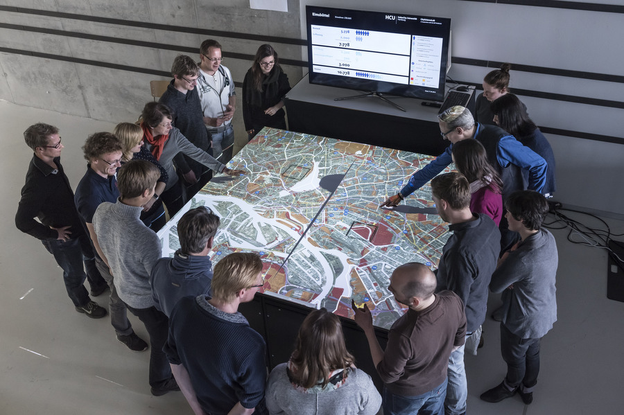 Durch eine spezielle Entwicklung wird ein Luftbild von Hamburg auf den Tisch projiziert. Foto: Walter Schießwohl