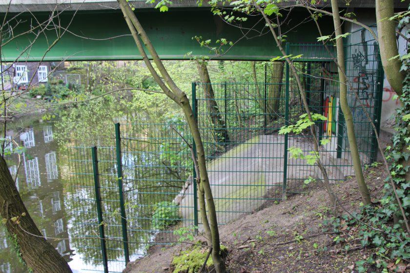 Der vom Bezirksamt am Isebekkanal errichtete Zaun, der Obdachlose fernhalten soll, muss wieder verschwinden. Foto: Niklas Rademacher