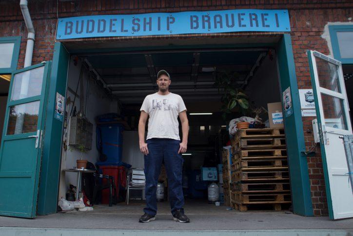 Simon Siemsglüss steht entspannt vor seiner kleinen Brauerei Buddelship in der Warnstedtstraße. Foto: Holger Vogel