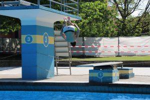 ... übt schon mal fleißig Saltos vom einer. Er freut sich über die Erfrischung im kühlen Freibad-Wasser. Foto: Max Gilbert