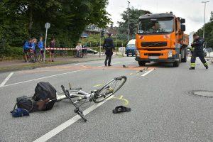 Das kaputte Fahrrad liegt vor dem orangenen LKW. Foto: Jonas Walzberg