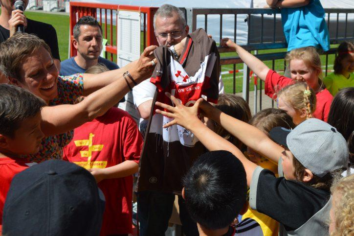 Die Reginalsportbeauftragte für Eimsbüttel Svenja Hornung übergibt einen der Preise der Mini-WM - ein Tricot mit den Unterschriften der St. Pauli-Spieler. Foto: Margarita Ilieva