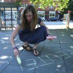 Rieke Guhl, Initiatorin von #therapeutenamlimit in Hamburg, malt den Slogan mit Kreide auf die Straße. Foto: Monika Dzialas