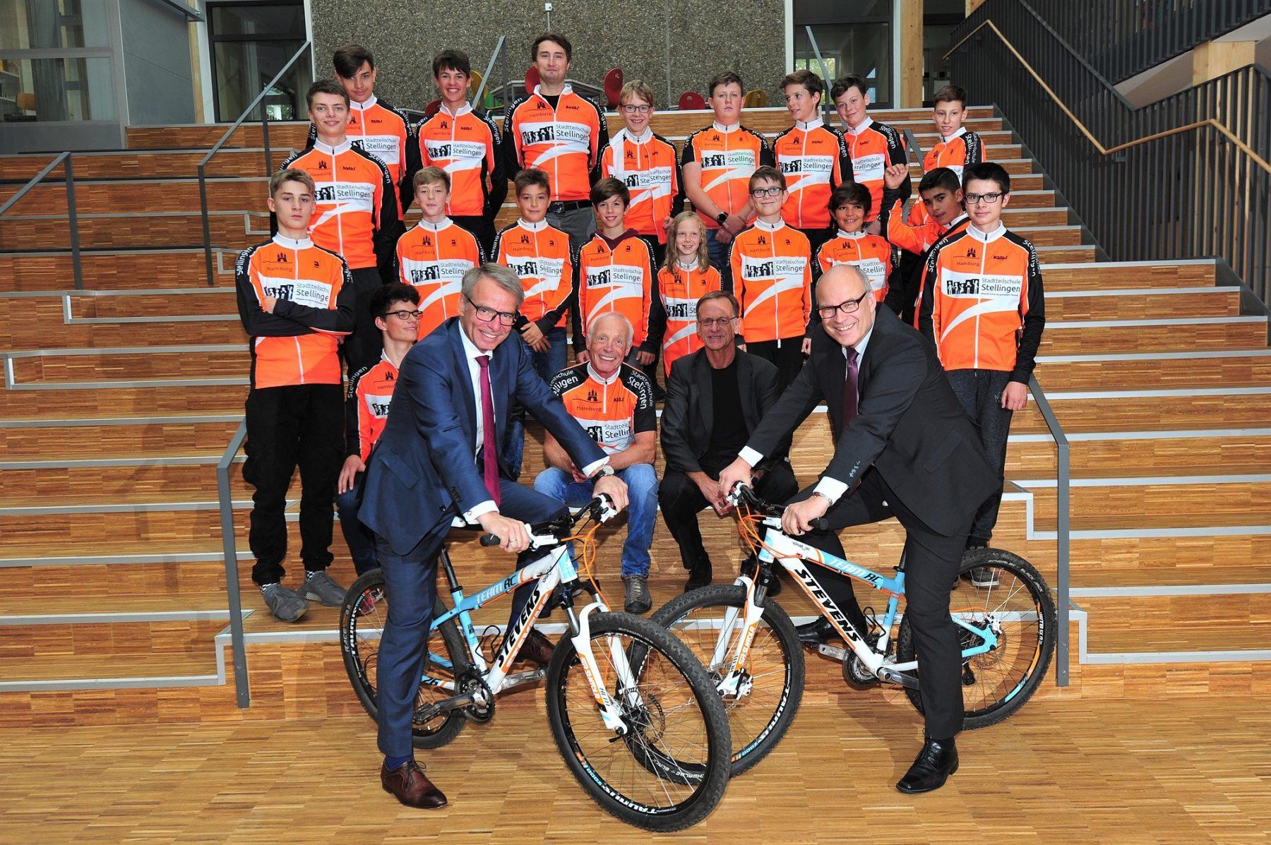 Stephan von Bülow, Vorsitzender der Geschäftsführung der Block Gruppe (links auf dem Rad) und Ties Rabe (ebenfalls auf dem Rad) mit Schülern der Radsportgruppe bei der Spendenübergabe. Foto: Block Gruppe / Patrick Piel