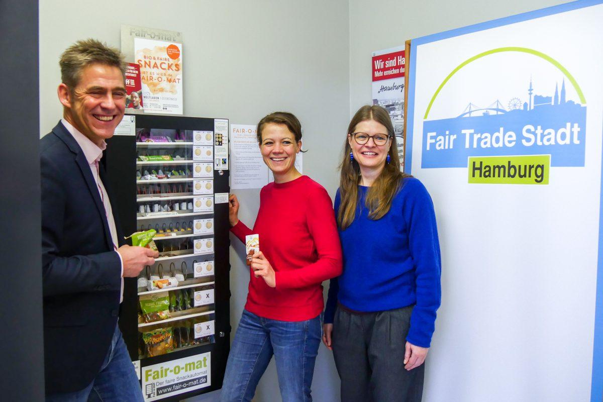 Herr Gätgens, Frau Putz und Frau Priessner ziehen die ersten fairen Snacks aus dem Fair-o-mat; Foto: Weltladen Osterstraße / Magdalena Gassner
