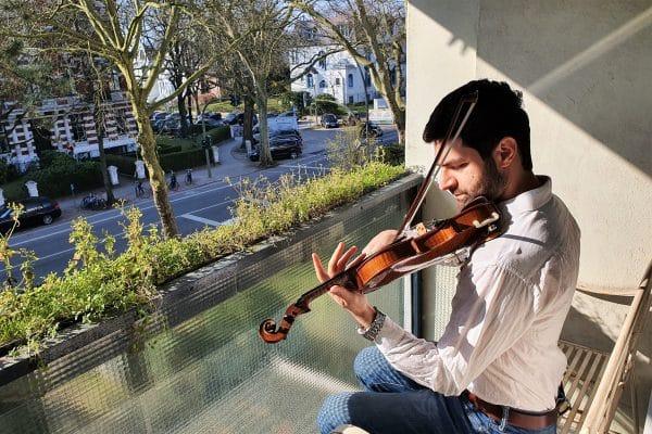 Der Geigenlehrer Ghaleb Jazmati gibt ein Benefiz-Konzert von seinem Balkon aus. Foto: Christa Eichelbauer